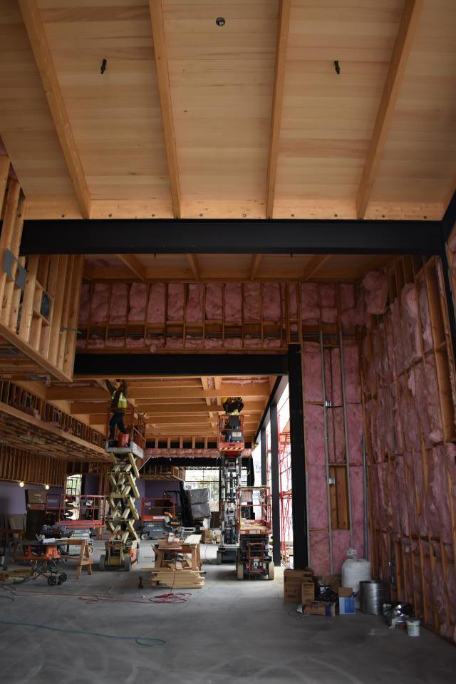 Electrical, lighting, and ceiling paneling is being installed in the front portion of the bakery area.